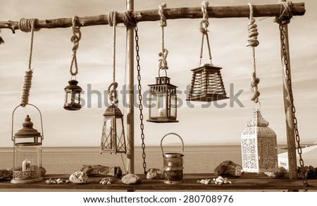 Lanterns hang near the sea on sepia tone - stock photo