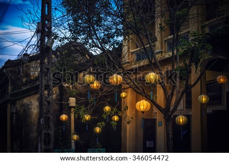 Lanterns  hanging on tree in Hoi An. Traditional asian lamps made of paper. Yellow wall of old building with two small windows. Equipment for cultural events in Vietnam, Asia. - stock photo