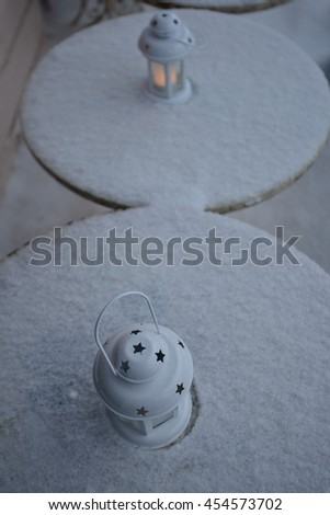 lanterns on table covered by snow