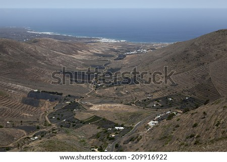 Lanzarote, Canary islands; A view from the pass with Los Helechos restaurant towards the town Arrieta. Several fields covered with almost black volcanic lapilli can be observed - stock photo
