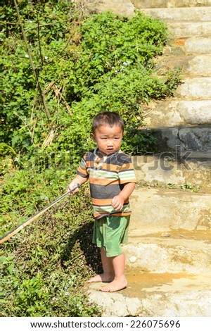 LAO CHAI VILLAGE, VIETNAM - SEP 22, 2014: Unidentified Hmong little boy plays with a bow in a village Lao Chai in Vietnam. Hmong is on of the minority eethnic group in Vietnam - stock photo