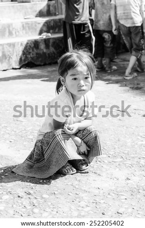 LAO CHAI VILLAGE, VIETNAM - SEP 22, 2014: Unidentified Hmong little girl sits on the ground on a break in a local primary school. Hmong is on of the minority eethnic group in Vietnam - stock photo