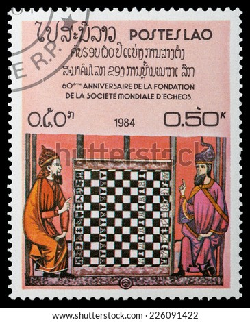 LAOS-CIRCA 1984: A stamp printed in Laos shows 60 anniversary of the World Chess Federation, chess games, circa 1984 - stock photo