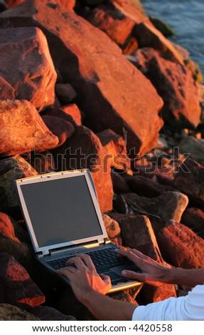 Laptop among rocks with hand - stock photo
