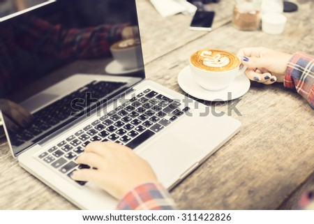 Laptop and a girl with cappuccino outdoor - stock photo