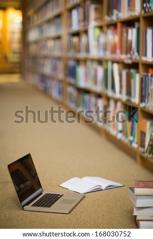 Laptop and books on the floor of library in college - stock photo