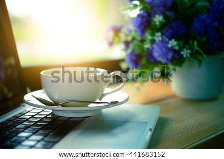 laptop and coffee cup in cafe, add flare - stock photo