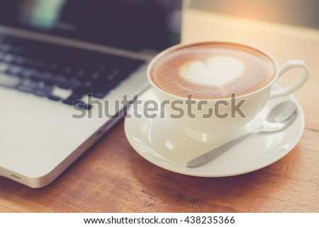 Laptop and coffee cup on wooden table with vintage filter - stock photo