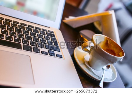 Laptop and cup of coffee on a table - stock photo