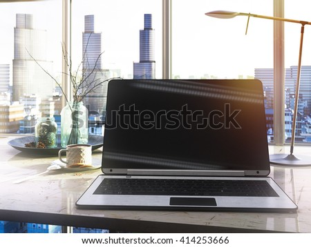 laptop and cup on the table in office through the window glass conceptual background - stock photo