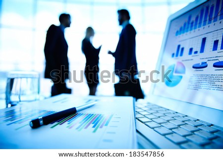 Laptop and financial document with pen at workplace on background of three business partners interacting - stock photo