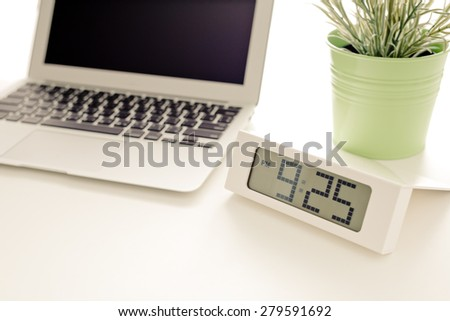 Laptop and flower pot with clock - stock photo