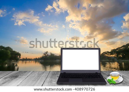 Laptop and hot tea on the old wood table at reservoir  with suns - stock photo