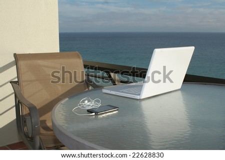 Laptop and media player refecting on glass with ocean view - stock photo