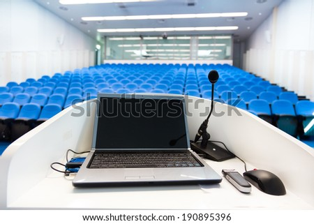 Laptop and microphone on the rostrum in empty conference hall with blue velvet chairs. - stock photo