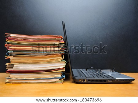 Laptop and office files on wooden table in front of black wall - stock photo