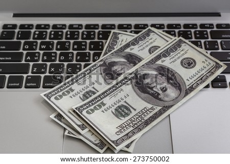 laptop and one hundred dollar banknotes on wooden table.