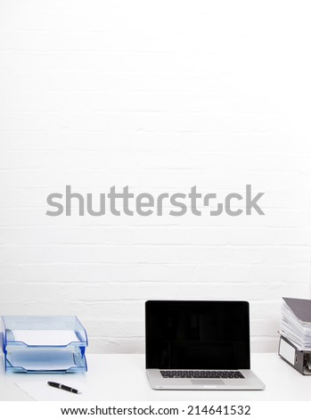 Laptop and paper tray on office desk - stock photo