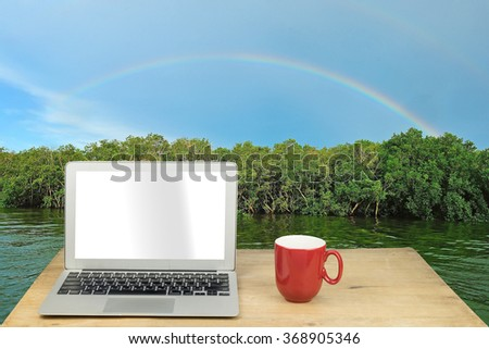 laptop and red mug on wood table with rainbow in mangrove forest - stock photo