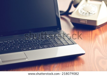 laptop and retro phone on office table - stock photo