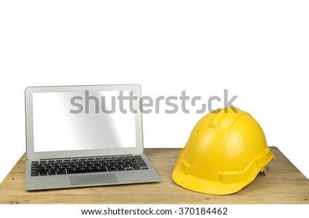 laptop and safety helmet on wood table with white background - stock photo