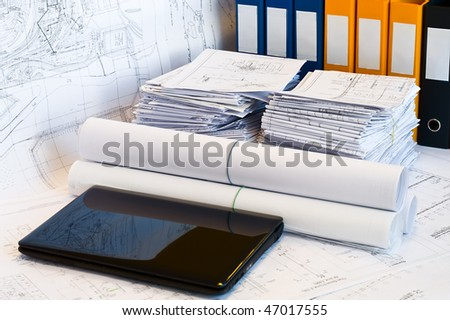 Laptop and stack of project drawings. Rolled papers. Working place. White screen - stock photo