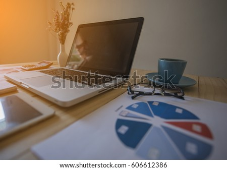 Laptop, coffee cup with financial documents on wooden table