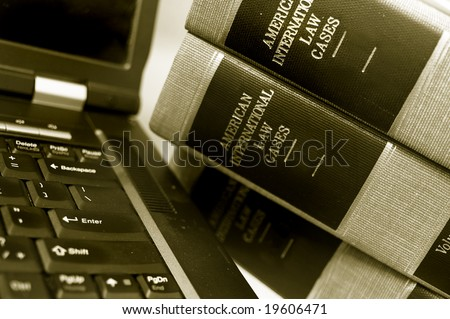 laptop computer and a stack of law books - stock photo