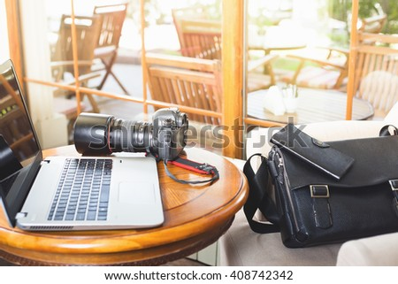 Laptop computer and dslr camera at cafe. Photographers profesional equipment. There are bag and wallet.