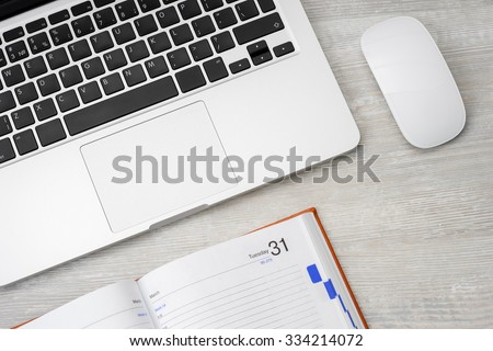 Laptop computer and mouse on a wooden desk, top view copy space - stock photo