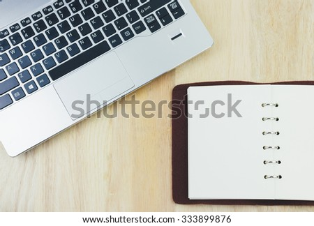 Laptop computer and notebook on a wooden desk. View from above with copy space. film tone - stock photo