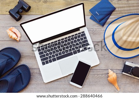 Laptop computer and smart phone with male summer holiday accessories on wooden board - stock photo