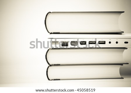 laptop computer between books - stock photo