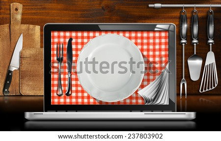 Laptop Computer in the Kitchen. Black and metallic laptop computer with empty plate and cutlery on red and white checkered tablecloth in a kitchen with cutting boards and utensils on wooden wall - stock photo