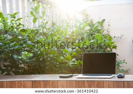 Laptop computer mock up with hard disk on wood texture in garden, right of frame. Relax from work.Fresh air. - stock photo