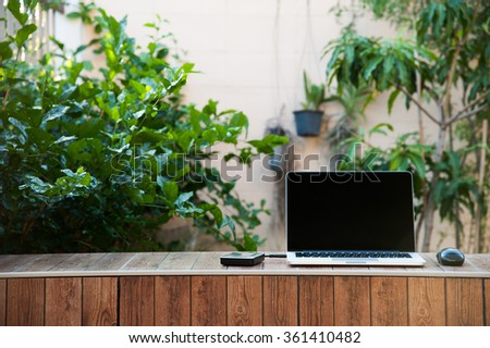 Laptop computer mock up with hard disk on wood texture in garden, right of frame. Relax from work. - stock photo