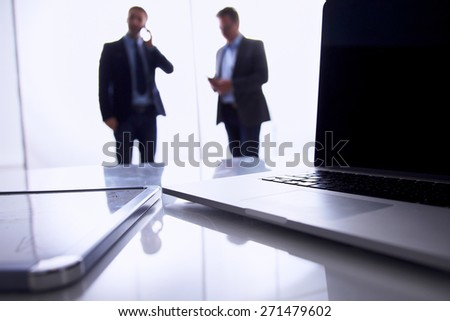 Laptop  computer on  desk , two businesspeople standing in the background