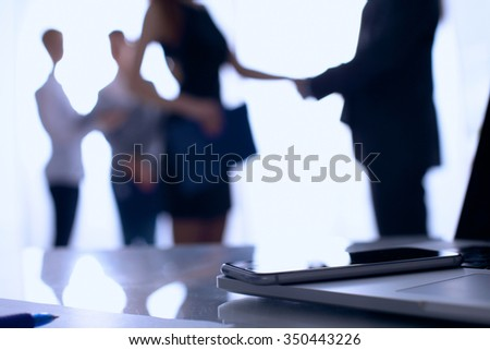 Laptop  computer on the desk ,businesspeople standing in the background. - stock photo