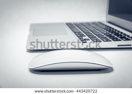 Laptop computer on white table with mouse. Filters added. - stock photo