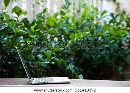 Laptop computer on wood texture in garden, left of frame,right space of frame. - stock photo