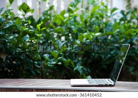 Laptop computer on wood texture in garden, right of frame, left space of frame. - stock photo