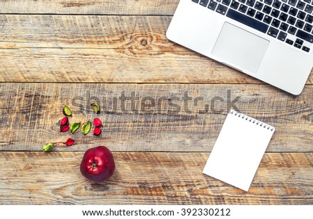 Laptop computer on wooden background with apple fruit. - stock photo