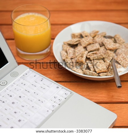 Laptop computer, orange juice & a bowl of cereal - starting the day in the digital age! - shallow dof - stock photo