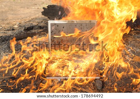 Laptop Computer setting the world on fire - stock photo