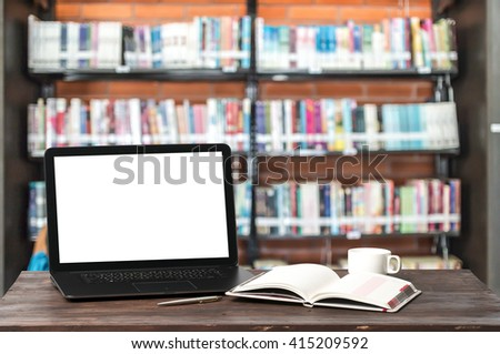 Laptop computer with a blank screen of old books in a library. - stock photo