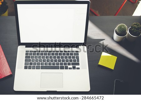 Laptop computer with blank copy space screen for your information or content, on-line learning or distance work concept, modern notebook on black table, freelancer workplace with stickers and phone - stock photo