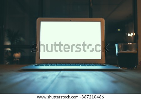 Laptop computer with blank screen on vintage wooden table. - stock photo