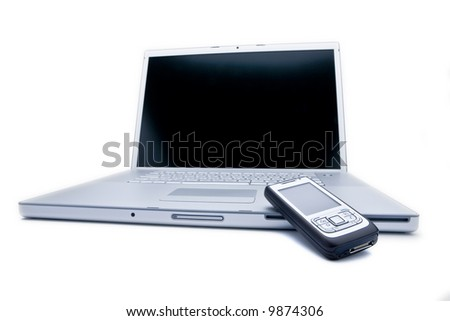 Laptop computer with cell phone on it