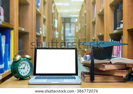 Laptop computer with clock, old books and graduation cap on the wood table in library, Education concept - stock photo