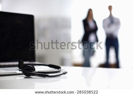 Laptop  computer with headset on the desk ,two  businesspeople standing in the background.